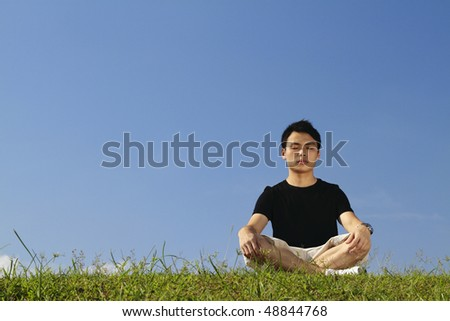 A young Asian man meditating outdoors on a sunny day