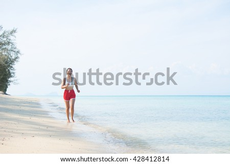 A young Asian woman exercises, running along a tropical beach. Fitness and vacations.