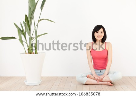 a young asian woman exercising in the living room - stock photo