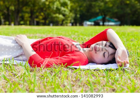 a young asian woman relaxing on  the grass