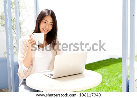 a young asian woman using laptop compute in cafe - stock photo