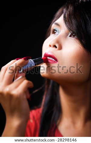 A young Asian woman using lipstick while looking away. Very shallow depth of field - focus on lips, contrast against dark room.