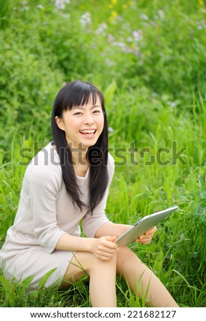 a young asian woman using tablet computer in the park
