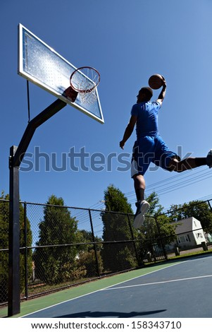 A young athlete flying through the air to dunk the ball into the basket. - stock photo