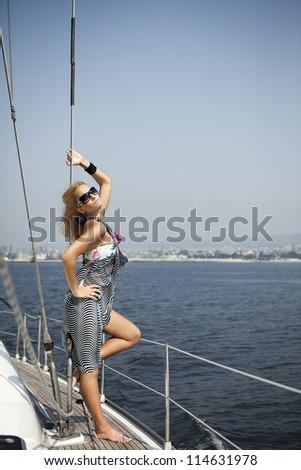 A young athletic woman hangs on the shrouds of a sailing yacht