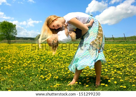 a young, attractive blond mother is laughing as she dances and plays outside with her happy baby child in a field of Dandelion flowers. - stock photo