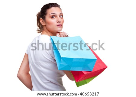 A young attractive brunette woman carrying some colorful shopping bags as she looks back over her shoulder, isolated on a white background. Blank bags for your own message. - stock photo