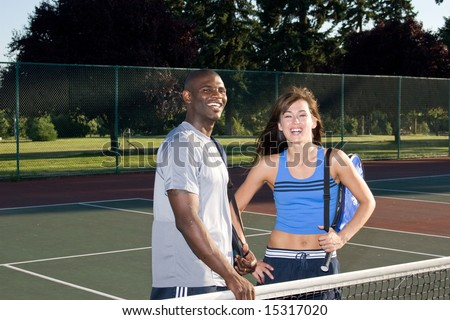 A young, attractive couple is standing together on a tennis court.  They are wearing tennis clothes, smiling, and looking at the camera.  Horizontally framed shot.