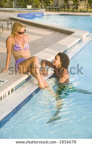 A young attractive couple play flirtaciously at the pool