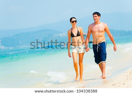 A young attractive couple walking hand in hand on a deserted tropical beach - stock photo