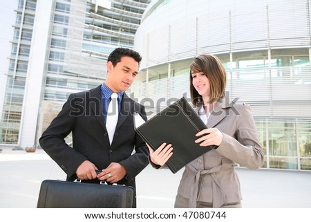 A young, attractive man and woman business team at their office building