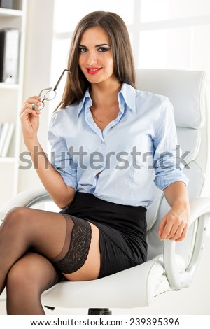 Straightforward Advice For Perfect Wife Online Across The Uk stock photo a young attractive woman in a short skirt sits cross legged in office armchair holding glasses 239395396
