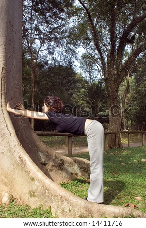 A young, attractive woman is standing next to a tree.  She is looking at the tree, leaning against it and stretching.  Vertically framed photo.