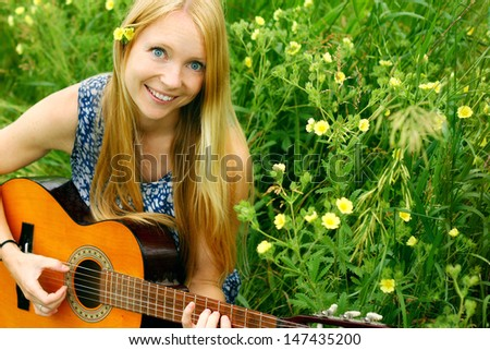 A young, attractive woman playing guitar outside in the grass and flowers - stock photo