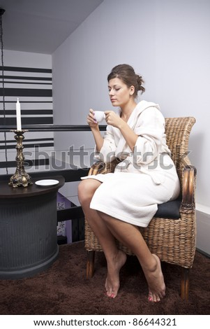 A young attractive woman sitting with a coffee - stock photo