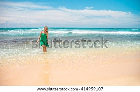 A young attractive woman standing on the ocean beach