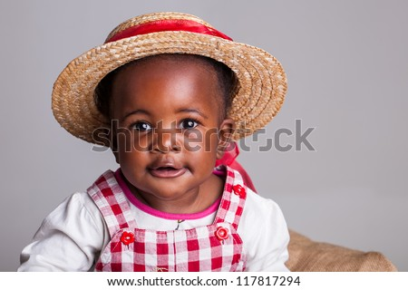 A young, baby farm girl with a straw hat and red ribbon. - stock photo