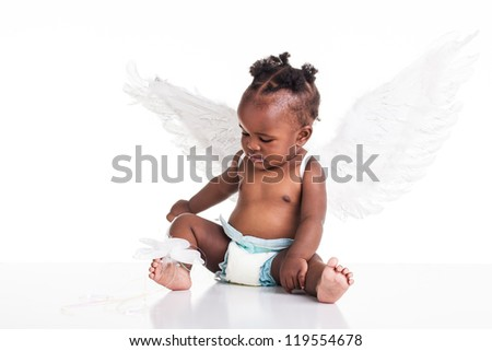 A young baby girl in her nappy with her wings and magic wand. - stock photo