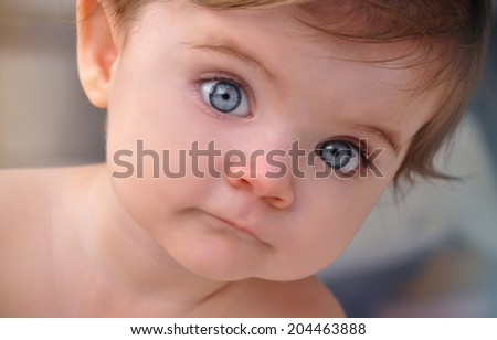 A young baby is looking at the camera with blue eyes. Use it for a child or parenthood concept.  - stock photo