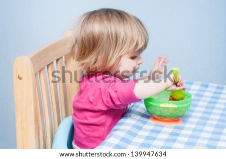 A young baby sits at the table and feeds herself from a bowl.