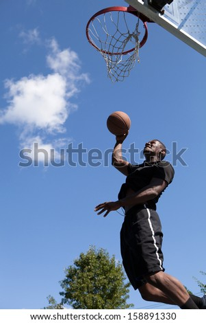 A young basketball flying through the air towards the rim for a dunk. - stock photo
