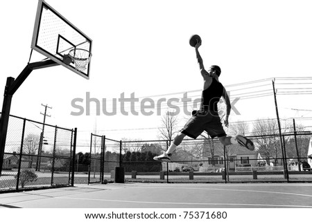 A young basketball player flying towards the rim for a slam dunk. - stock photo