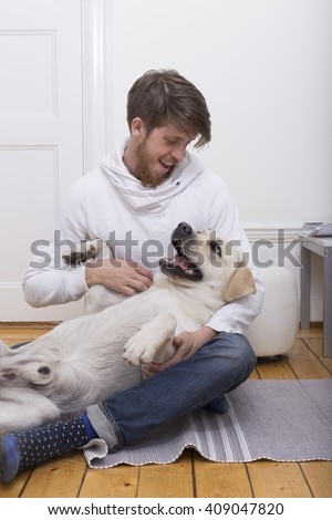 a young bearded man playing with his yellow labrador retriever indoors in the apartment - stock photo