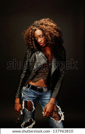 A young beautiful african american female holds a semi automatic pistol during this dark photo shoot against black - stock photo