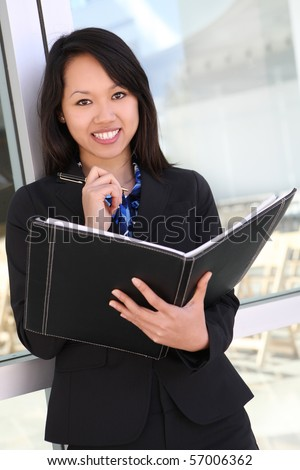 A young, beautiful asian business woman at office with notebook - stock photo