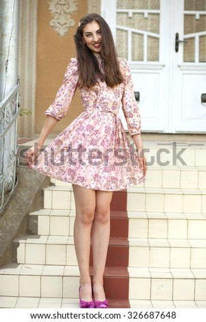 A young beautiful brunette model in romantic vintage floral dress and rose stone accessories and cute shoes posing on stairs of a nice house in summertime.  - stock photo