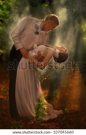 A young beautiful couple dance in a forest - stock photo