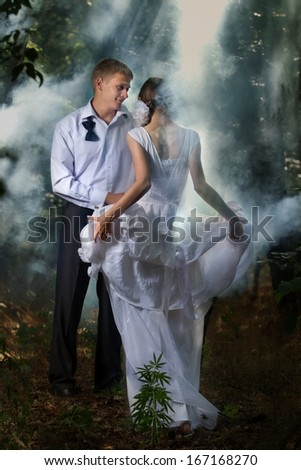 A young beautiful couple in a forest - stock photo