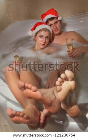 A young beautiful couple in santa hats is enjoying a bath