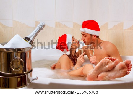 A young beautiful couple in santa hats is enjoying a bath - stock photo