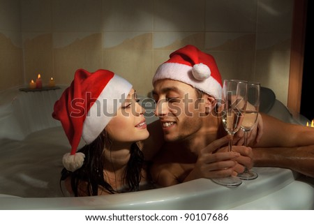 A young beautiful couple in santa hats is enjoying a bath with champagne in a glasses - stock photo
