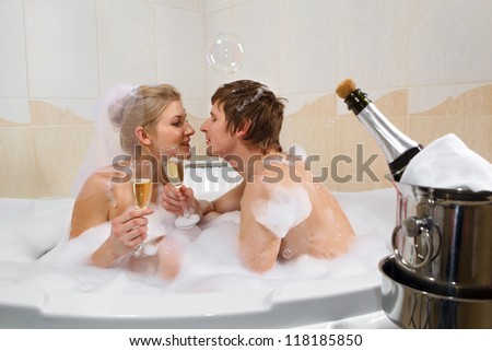 A young beautiful couple is enjoying a bath with champagne in a glass and kissing. Bubbles are floating in the air - stock photo