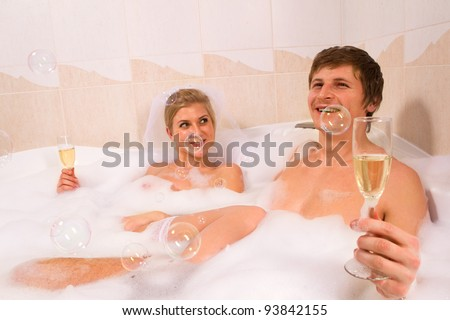 A young beautiful couple is enjoying a bath with champagne in a glass and looking at bubbles that are floating in the air - stock photo