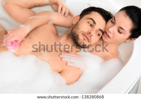 A young beautiful couple is taking a bubble bath - stock photo
