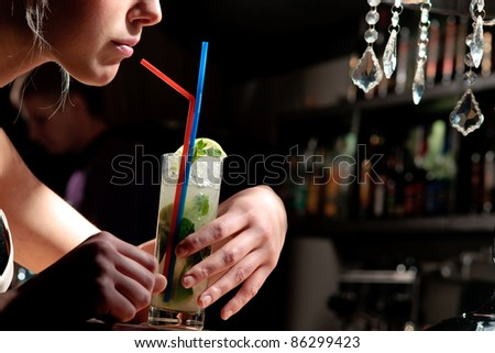 A young beautiful girl drinking cool mohito with a straw in a cafe - stock photo