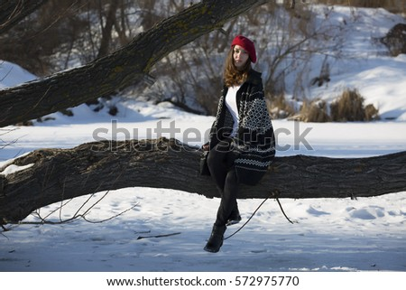 a young beautiful girl in a red beret against the background of a winter landscape on a sunny day
