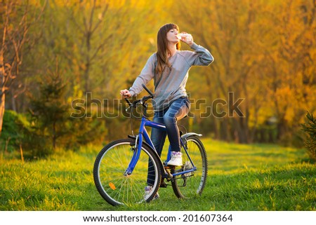 A young beautiful girl is drinking water from a bottle while sitting on a bicycle - Outdoors at sunset - stock photo