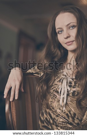 A young beautiful girl waiting for a cup of tea in a cafe, cappuccino toning - stock photo