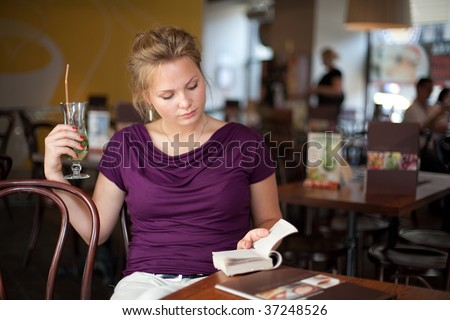 A young beautiful girl with cocktail glass reading book in the coffee house