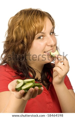 a young, beautiful, happy woman is holding some cucumber in front of her face - stock photo