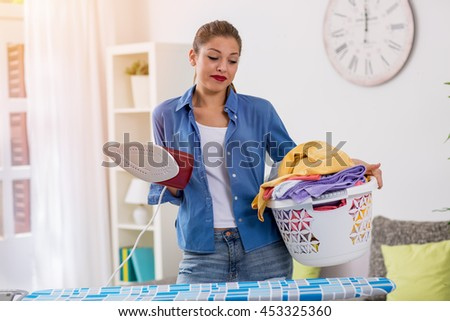 A young beautiful housewife holding iron and basket with clothes - stock photo