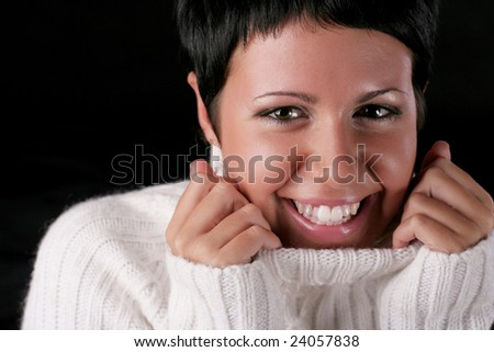 A young beautiful laughing woman wearing white sweater over black background - stock photo