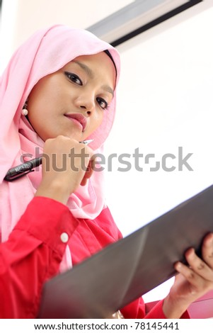 A young beautiful muslim girl holding a report file - stock photo