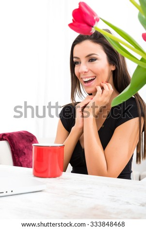 A young beautiful woman being cheerful while using a Laptop computer at home. - stock photo