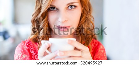 a young beautiful woman in red dress is drinking coffee in a cafe