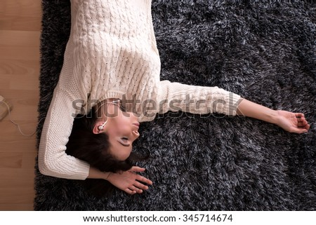 A young beautiful woman in underwear lying on a carpet and listening to music
